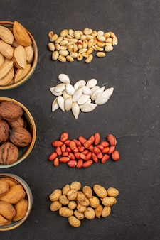 Top view of nut composition with different fresh nuts on dark surface
