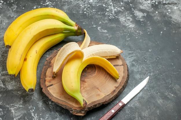 Vista dall'alto fonte di nutrizione pacco di banane fresche e sbucciate su tagliere di legno coltello su sfondo grigio