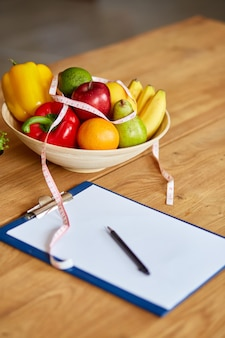 Top view of nutritionist, dietitian workplace with measuring tape and bowl with healthy vegetables and fruits