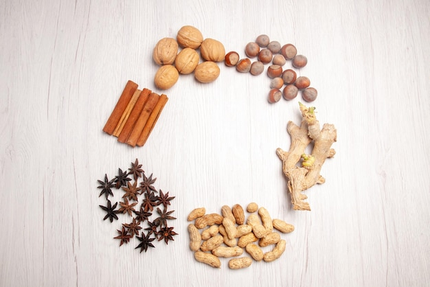 上面図ナッツとシナモンシナモンスティックとさまざまな種類のナッツが白いテーブルの上に円形に配置されています