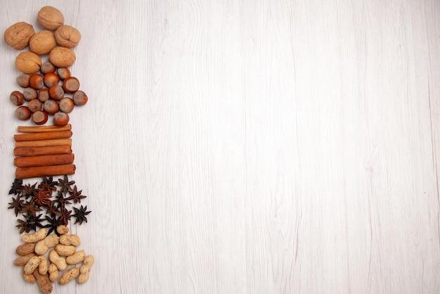 흰색 테이블 왼쪽에 있는 상위 뷰 견과류와 계피 계피 스틱 땅콩 호두 헤이즐넛