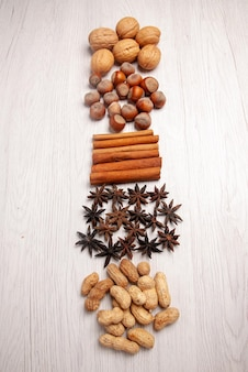 Top view nuts and cinnamon different kinds of nuts and cinnamon sticks on the white table