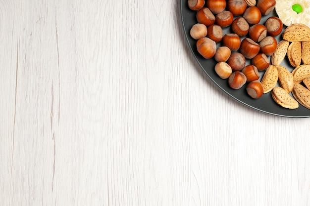 상위 뷰 견과류 구성 신선한 호두 땅콩과 밝은 흰색 책상 너트 스낵 식물 나무 많은 껍질에 접시 안에 헤이즐넛
