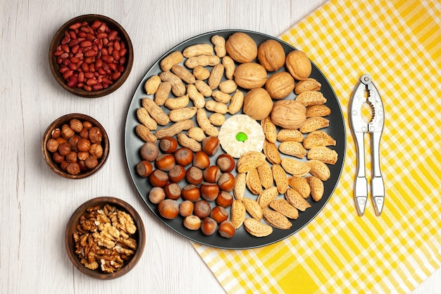 상위 뷰 견과류 구성 신선한 호두 땅콩과 흰색 책상 너트 나무 스낵 공장 많은 껍질에 접시 안에 헤이즐넛