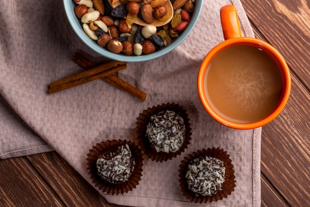 Top view of nuts mix chocolate muffins and a mug of cocoa drink on rustic