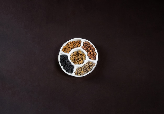 Top view nuts plate with dry fruits on a black table.