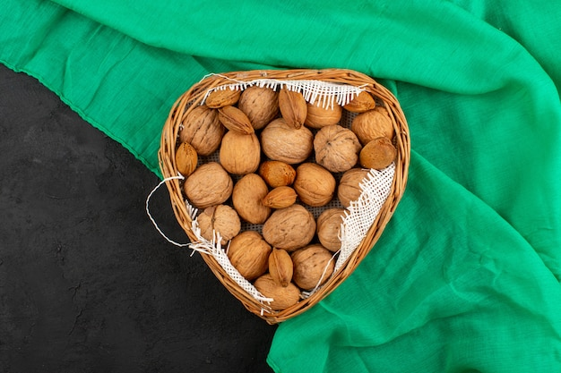 Top view nuts walnuts inside brown basket on the green tissue and grey