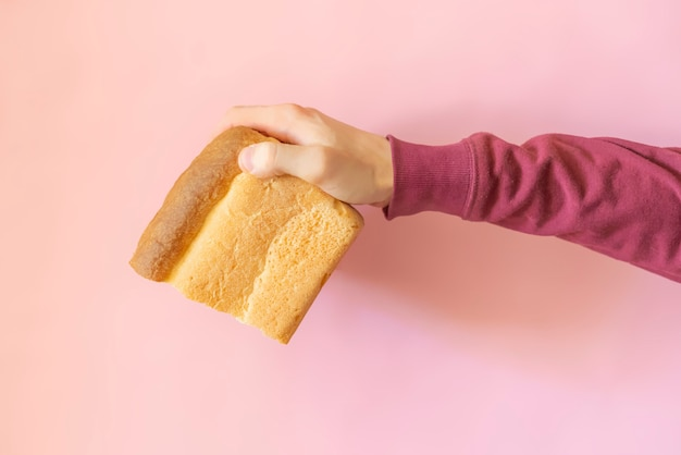 Top view o person's hand holding a loa bread  over the color background