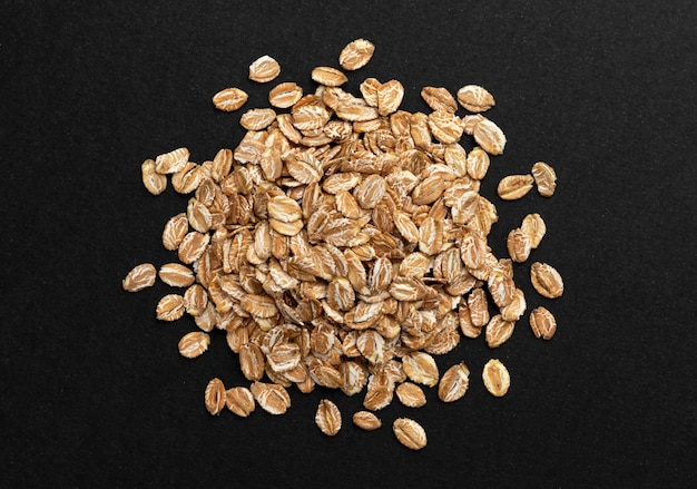 Top view of oat flakes on black background