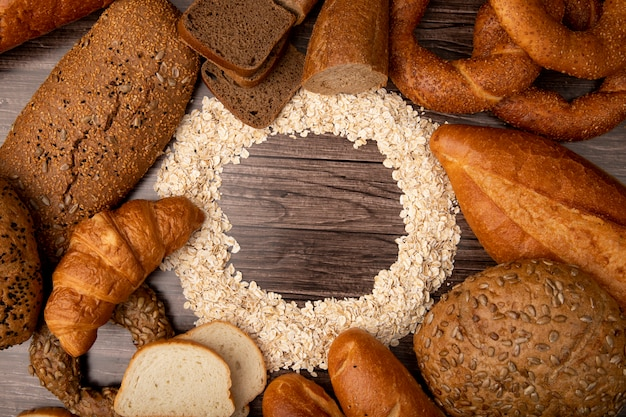 Top view of oat-flakes set in circular shape and breads around as baguette rye white cob bagel on wooden background with copy space