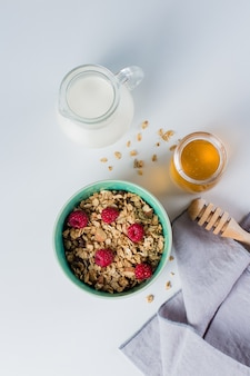 Top view of oat granola with nuts and raspberry, milk and honey on white background