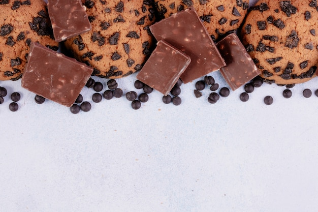 Top view of oatmeal cookies with chocolate chips and dark chocolate pieces on white background with copy space