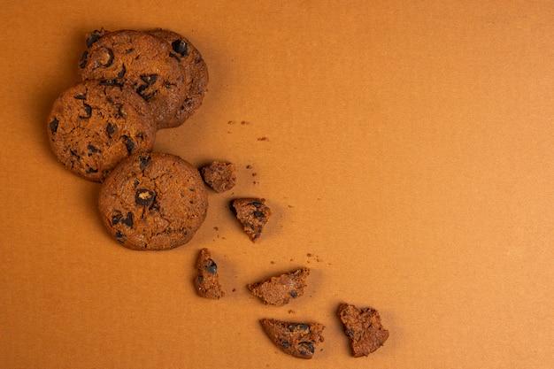 Vista dall'alto di biscotti di farina d'avena con gocce di cioccolato cadere rotto con copia spazio su ocra