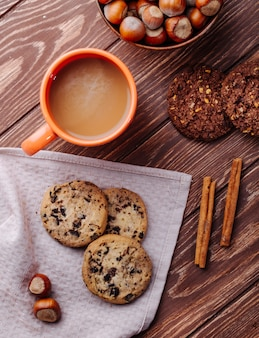 Top view of oatmeal cookies with chocolate chips and a mug of cocoa drink on a wooden