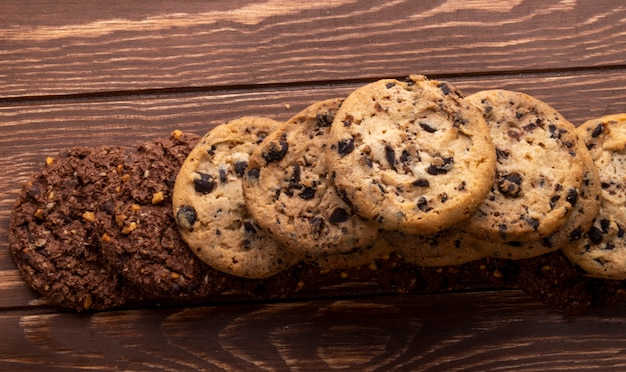 Top view of oatmeal cookies with chocolate chips nuts and cocoa on a wooden