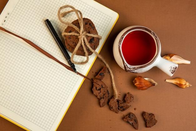 Vista dall'alto di biscotti di farina d'avena con gocce di cioccolato e aprire il taccuino vuoto con penna e una tazza di tè su ocra