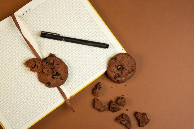 Vista dall'alto di biscotti di farina d'avena con gocce di cioccolato e aprire il taccuino vuoto con la penna sull'ocra