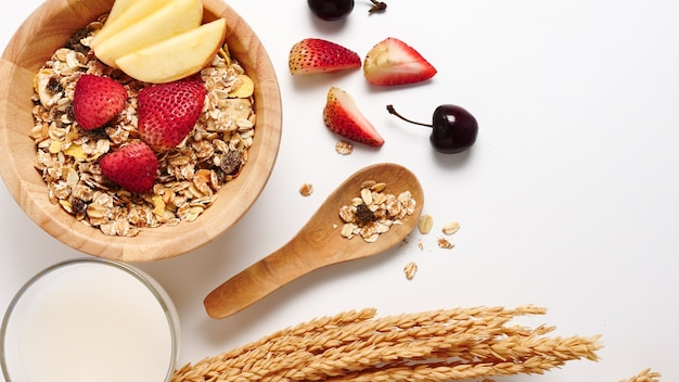 Top view of oatmeal flakes, milk, and fresh fruits on white background. copy space