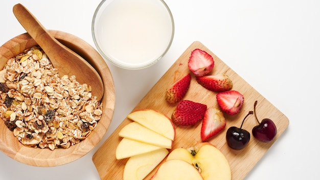Top view of oatmeal flakes, milk, and fresh fruits on white background.