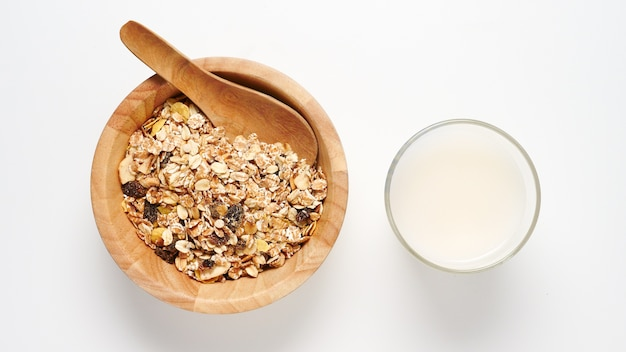 Top view of oatmeal flakes and milk on white background.