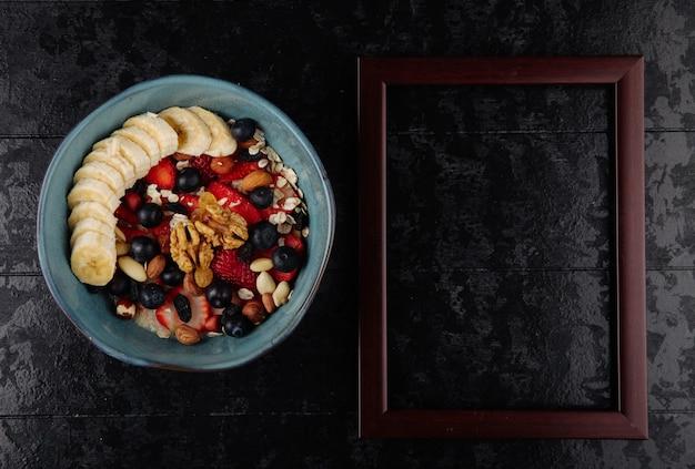 Vista superiore del porridge di farina d'avena con bacche di banane e noci e cornice vuota in legno su sfondo nero