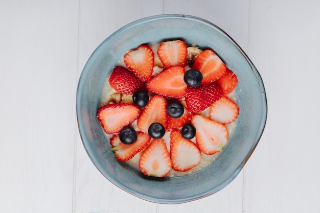 Top view of oatmeal porridge with sliced strawberries and blueberry in a ceramic bowl on white table