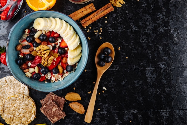 Top view of oatmeal porridge with strawberries blueberries bananas dried fruits and nuts in a ceramic bowl and wooden spoon with berries on black background with copy space