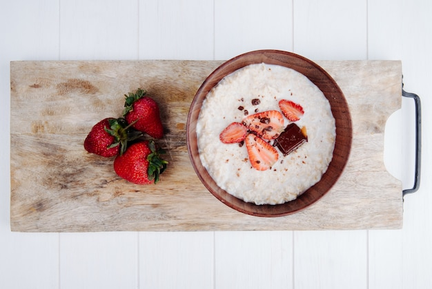 Top view of oatmeal porridge in a wood bowl with fresh ripe strawberries on wood cutting board on rustic