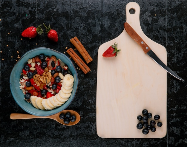 Top view of oatmeal porridge and wooden cutting board with kitchen knife on black background