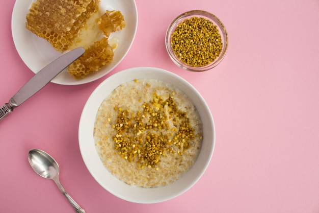 Top view of oatmeal with bee pollen and honey in bowl