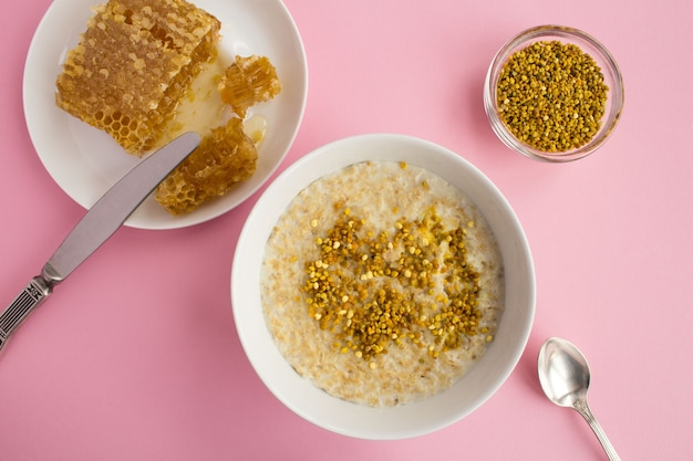 Top view of oatmeal with bee pollen and honey on the pink table