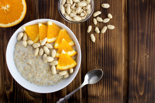 Top view of oatmeal with orange and peanuts