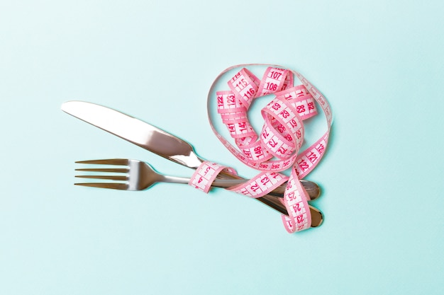 Top view of obesity concept with fork and knife wrapped in curled measuring tape on blue