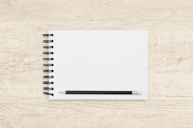 Top view object of blank notebook and pencil on wooden texture.