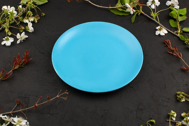 Top view ocean blue plate around white flowers on the dark floor