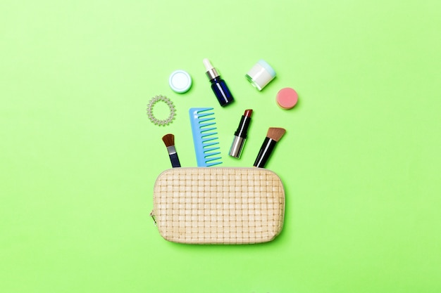 Top view od cosmetics bag with spilled out make up products on green