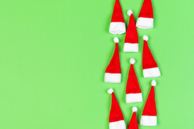 Top view od stylish red santa hats on colorful background. merry christmas concept with copy space.