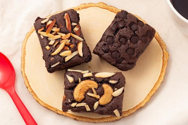 木製の受け皿にチョコレートチップ、アーモンド、ナッツ、ティータイム、コーヒータイム、または休憩タイムのスイーツが付いた3つの正方形のダークブラウニーの上面図。