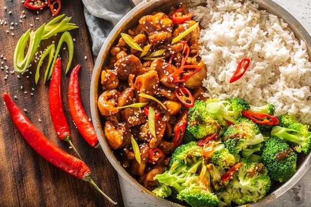 ヴィンテージテーブルにご飯、ブロッコリー、唐辛子を添えたアジアンスタイルの照り焼きチキンの上面図。