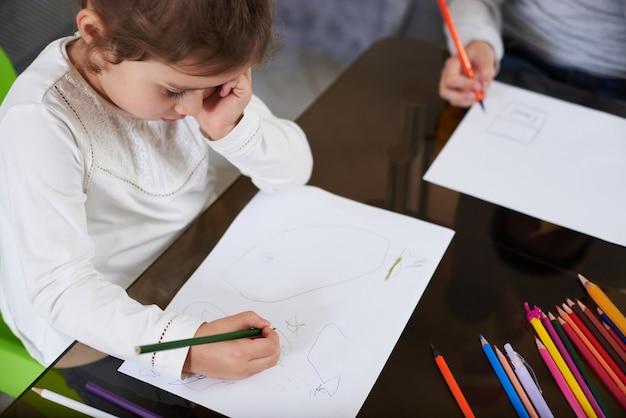 Вид сверху на девочку в белой рубашке, сосредоточенной на рисовании цветным карандашом. цветные деревянные карандаши, лежащие на столе.