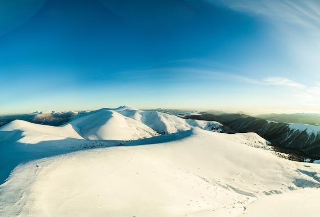 Вид сверху на красивый завораживающий вид на горнолыжный склон с расположенными в горах лыжными трассами в солнечный зимний морозный вечер