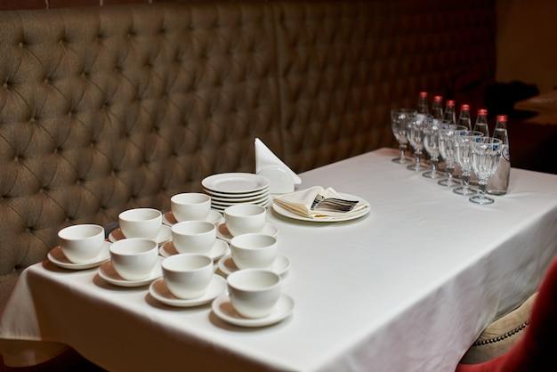 Вид сверху красиво оформленный стол с белыми тарелками, чайные сервизы, столовые приборы