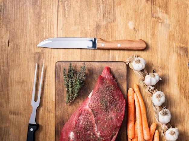Вид сверху на большой кусок красного мяса рядом с чесноком, морковью и ножом повара в центре кадра. приготовление еды. натуральный протеин.