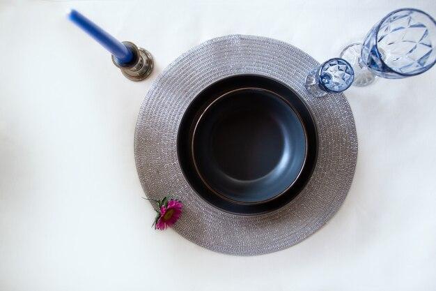 Вид сверху черной тарелки с синими очками и свечами.