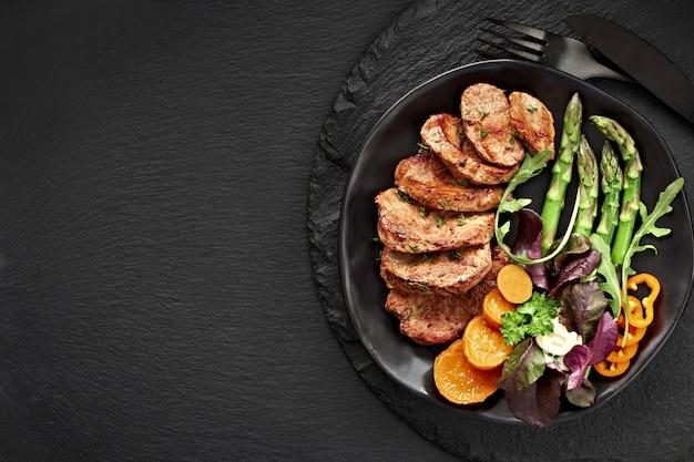 Вид сверху на черную тарелку с жареными кусочками говядины, сладкого картофеля и смешанного салата на черном сланцевом камне