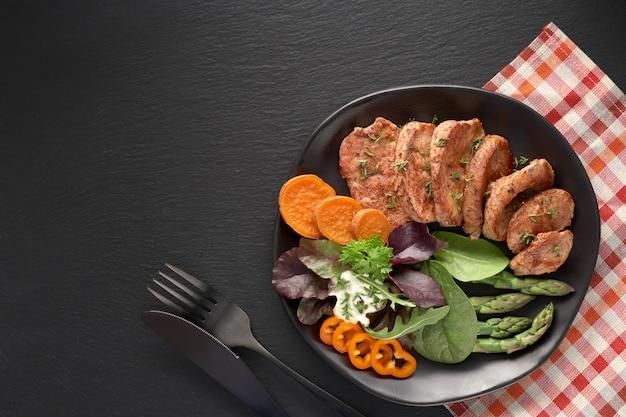 黒いスレートに牛肉、サツマイモ、ミックスサラダのフライドスライスの黒い皿の上から見る