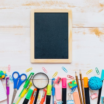 Top view of a blackboard with school supplies on white background