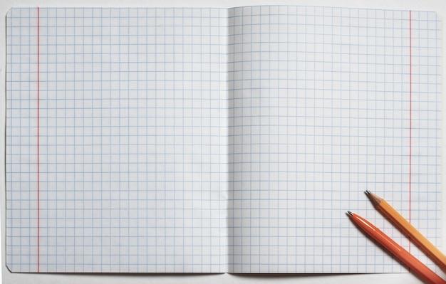 Вид сверху пустого открытого квадрата тетради, ручки и карандаша. плоская планировка, копия пространства. снова в школу концепции. бизнес-концепция
