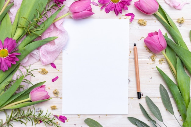Вид сверху на чистый лист бумаги и карандаш, украшенный фиолетовыми цветами