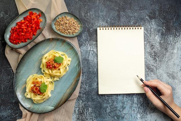 スパイラルノートにペンを持ってその材料の手が日焼け色のタオルで夕食にトマトと肉と一緒に出されるおいしいパスタの食事と青いプレートの上面図